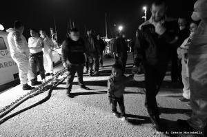 Il comandante del porto di Roccella, T.V. (CP) Massimiliano Santodirocco, Cammina sulla banchina del porto con uno dei più piccoli migranti giunti questa notte.