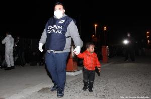 Questo bambino ha preso per la mano un uomo della Guardia Costiera, Antonio, e ha passeggiato sulla banchina per tutte le ore di attesa prima di essere trasferiti in un ricovero.